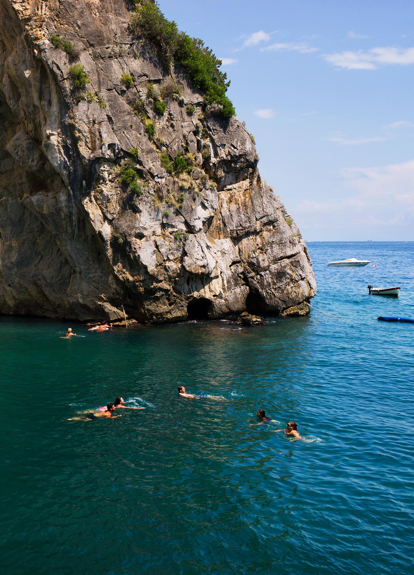 people swimming below a cliff